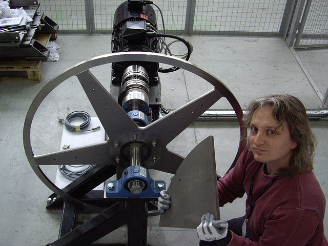Ian Bailey holds one of the wheel's off-cuts next to the rotating positron target prototype.  Off-cuts are used for wheel material studies.  A motor sits behind the wheel.