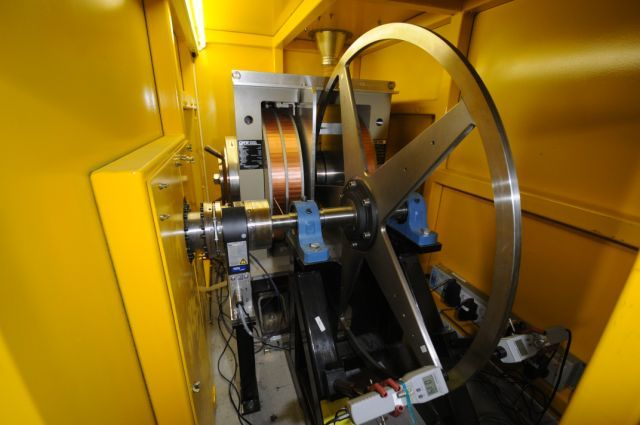 The rotating positron target sits in a protective steel bunker.  A dipole magnet (rear) creates a one-tesla magnetic field to help with tests related to eddy currents.  The two light grey boxes in the foreground measure the wheel rim's temperature.  Image courtesy of Ian Bailey.