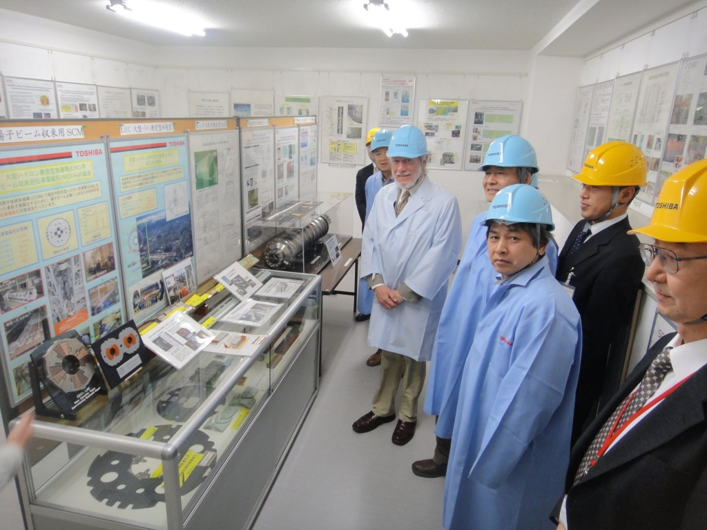 Project Managers Marc Ross and Akira Yamamoto at the Toshiba company in Japan. They stand in front of a display case of magnet windings and a test cavity. Image: Akira Yamamoto