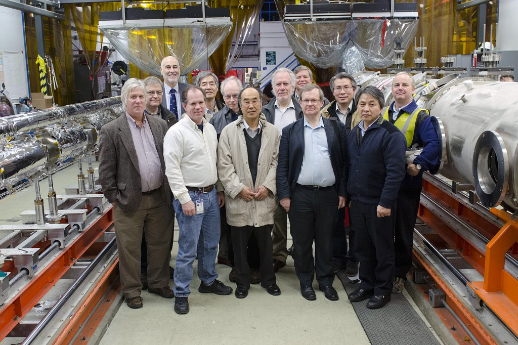 Members of the GDE Executive Committee pause during a tour of Jefferson Lab's Institute for Superconducting Radiofrequency Science and Technology for a group photo between two C100 cryomodules being built for Jefferson Lab's 12 GeV Upgrade. Image: Jefferson Lab