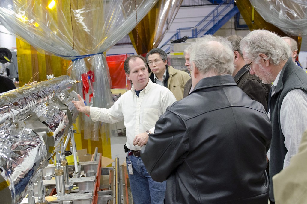 John Hogan, Jefferson Lab SRF Cryomodule Production Leader, shows GDE Executive Committee members the sixth C100 cryomodule (of ten) being produced at Jefferson Lab as part of the lab's 12 GeV CEBAF Upgrade Project. This cryomodule is at the cold-mass assembly stage and Hogan is discussing the integrated design of the components as they relate to overall cryomodule performance. Image: Jefferson Lab