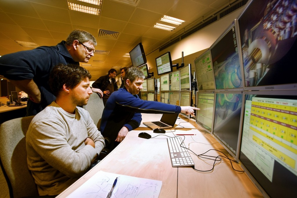 Julien Branlard, Nick Walker and John Carwardine discussing settings for the long bunch train studies in the accelerator control room at DESY.