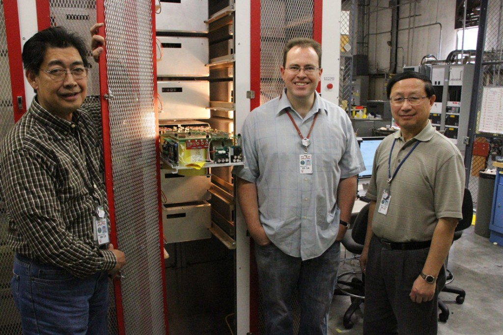 Alfred Viceral, Mark Kemp and Patrick Shen, who worked on the development of the Marx P2, stand in front of the enclosed modulator. One cell is pulled out of its drawer. Image: Ray Larsen